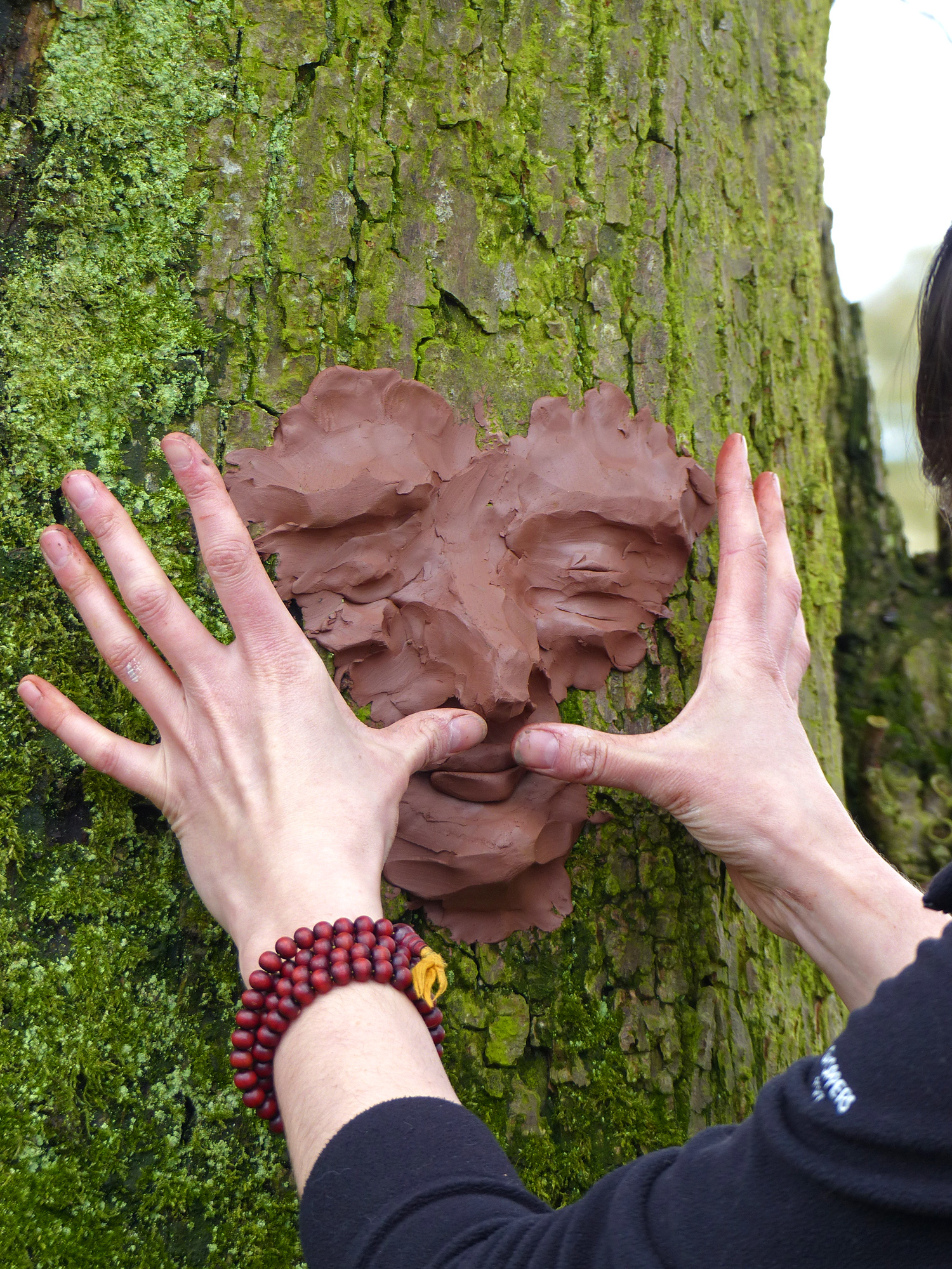 hands making clay face on a tree